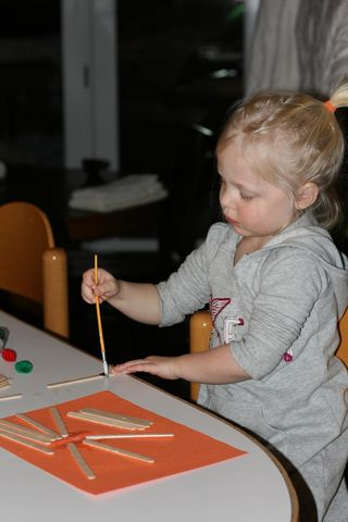 Ellie-making-crafts-from-glue-paper-popsicle-sticks